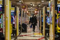 TOKYO, JAPAN - 16 FEB 2018: Woman walking and Japanese people playing in a Pachinko parlor of Shinjuku district
