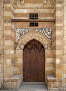 Wooden aged grunge door and stone bricks wall, one of the exterior doors of Aqsunqur Mosque (Blue Mosque), Bab El-Wazir District, Medieval Cairo, Egypt