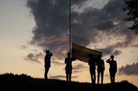 Soldiers Raising The Lithuanian Flag At Sunset