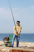 bearded fisherman with fishing rod on sea pier
