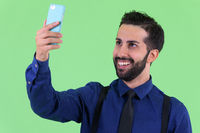 Young happy bearded Persian businessman taking selfie