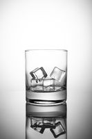 Empty rocks glass with ice-cubes, isolated on white background