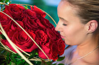 A woman with a romantic face sniffs at the red rose