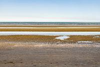 Oostduinkerke, Belgium - June 19, 2019: Layered minimalistic seascape with blue, green and orange tints