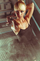 Blonde girl with pistols in an abandoned factory. cosplayer, action and dangerous woman
