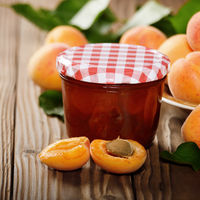 Glass Jar of Apricot jam on wooden table with ripe apricots aside