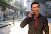 Happy Hispanic businessman thinking while talking on the phone outdoors