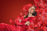 Fashion brunette woman relaxing in chair with big red flowers