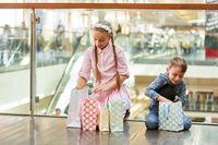 Zwei Kinder packen ihre  Einkaufstüten aus