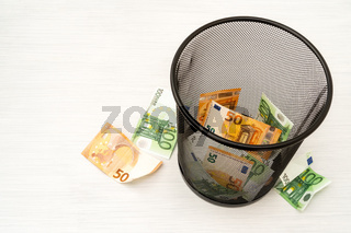 Money euro in bin