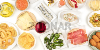 A panorama of Spanish tapas and wine, an overhead photo of a variety of snacks. Manchego cheese, jamon, padron peppers, sardines, squid rings, olives, shot from the top on a white background