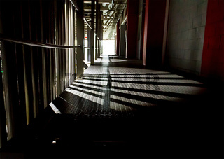 Dark long corridor on the side break through the rays of light against the background of the light window figure danger