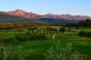 Golf Course with Alaska mountain range in the background and blue sky above during sunset golden hour alpenglow. Healy, North America, United States