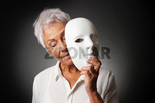 older woman hiding sad face behind mask