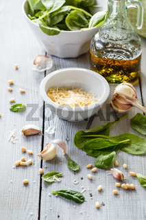 Spinach pesto in a glass jar, decoration: spinach leaves, pine nut, cheese Parmesan, garlic, olive oil.