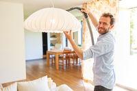 Hausmann beim Staubsaugen an Deckenlampe