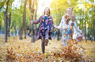Fashionable beautiful young girlfriends walking together in the autumn park background. Having fun and posing