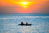 Sunset over sea and silhouette of kayak