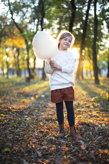 Little cute girl with cotton candy in the autumn park background. Having fun and posing
