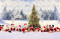 Santas in front of winter landscape with christmas tree