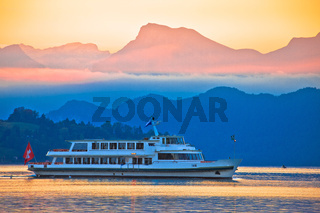 Lake Lucerne golden dawn boat and mountain peaks view,