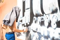 Writer working on a wall in an anonymous way