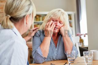 Ärztin tröstet weinende Patientin beim Hausbesuch