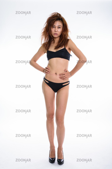 Full body shot of young Asian woman standing and posing while we