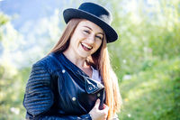 Young woman with leather jacket and hat in the garden - enjoying spring and sunshine in the green.