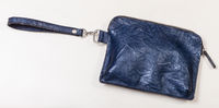 closed small wristlet purse bag on pale table