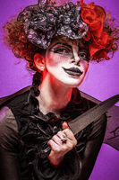 A closeup of a scarier clown female Holding Knife