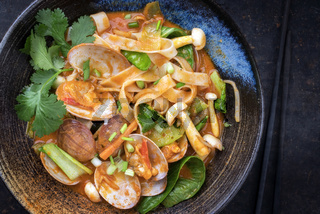 Traditional Thai kaeng phet red curry with clams and vegetable as top view in a bowl