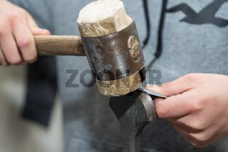 Handwerker bearbeitet Metall mit Holzhammer - Nahaufnahme falzen