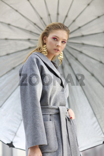 Fashion portrait of young elegant woman in Grey coat, black pants, black ankle boots and gold earrings