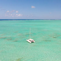 Aerial view of Catamaran boat sailing in turquoise lagoon of Ile aux Cerfs Island lagoon in Mauritius.
