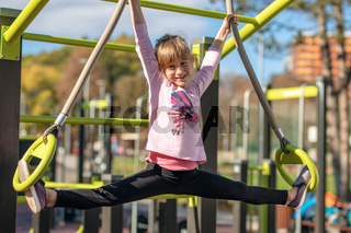 Young girl exercising splits on gymnastic rings outdoor