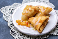 Crepes in the form of triangles stuffed with apples.