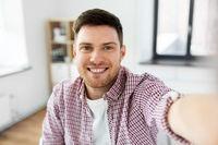 man or video blogger taking selfie