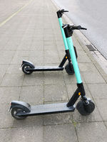 two electric kick scooters or e-scooter parked on sidewalk