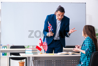 Male english teacher and female student in the classroom