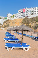 Rows of beach beds with thatched umbrellas