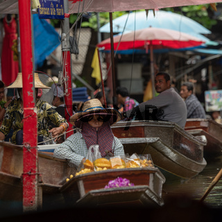 Woman with two hats in floating market