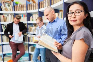Asiatische Frau beim Buch lesen in der Bibliothek