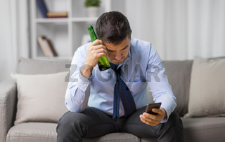 man with smartphone and bottle of beer at home