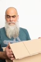 skeptical looking bearded man with a carton box