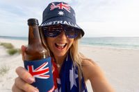 Australian culture - lazy day on beach girl with a beer