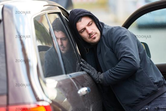 Mann als Dieb am offenen Auto