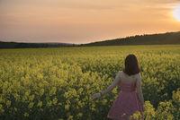Woman walking through rapeseed field at sunset