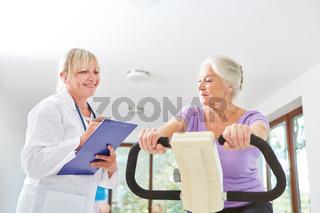 Senior Frau trainiert auf dem Ergometer