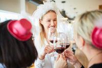 Glückliche Braut beim Anstoßen mit Glas Wein